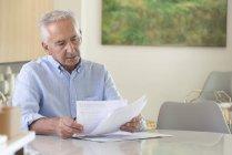 Hombre mayor enfocado haciendo papeleo en casa - foto de stock