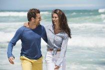 Пара прогулок по пляжу с волнистым морем на заднем плане — стоковое фото