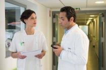 Doutor e enfermeira que discutem no corredor do hospital — Fotografia de Stock