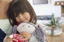 Крупный план маленькой девочки, сидящей с матерью и держащей тряпичную куклу — стоковое фото