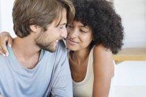Закри посміхаючись багатоетнічного пара в любові, дивлячись один на одного — стокове фото