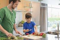 Homem olhando filho cortando legumes na cozinha — Fotografia de Stock