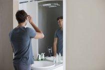 Jovem verificando o cabelo no espelho no banheiro — Fotografia de Stock