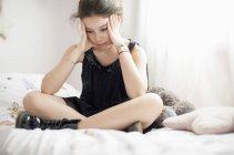 Серйозна Дівчинка-підліток сидить на ліжку — стокове фото