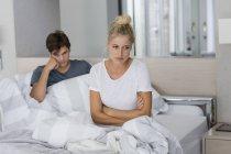 Jeune couple assis sur le lit avec des difficultés relationnelles — Photo de stock