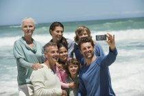 Portrait de la famille heureuse multi-génération prenant selfie avec téléphone portable sur la plage — Photo de stock