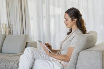 Woman using digital tablet on couch at home — Stock Photo