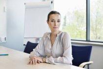 Portrait d'une femme d'affaires confiante assise au bureau — Photo de stock