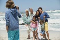 Menino tirando foto de família posando na praia arenosa — Fotografia de Stock