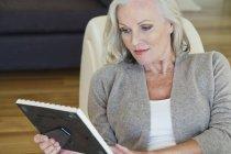 Старші жінки, дивлячись на фотографію рамку, сидячи на дивані в домашніх умовах — стокове фото