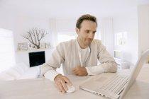 Uomo che lavora su laptop e sorride in appartamento moderno — Foto stock