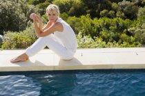 Мрійливий розслабленої жінка сидить біля басейну і дивлячись на воді — стокове фото