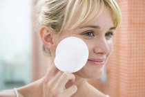 Smiling woman applying face powder with cotton ball — Stock Photo