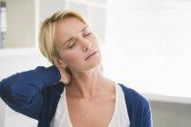 Donna stanca con gli occhi chiusi toccando il collo — Foto stock