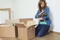 Woman holding cat on floor near cardboard boxes — Stock Photo