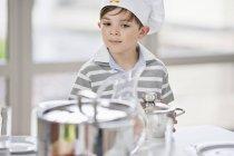 Продуманий маленький хлопчик розміщення каструлі на обідній стіл — стокове фото