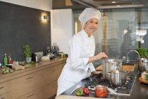 Woman in chef costume cooking food in kitchen — Stock Photo