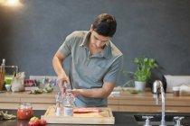 Чоловік дощування чорного перцю на м'ясо в сучасній кухні — стокове фото