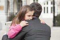 Симпатичні дівчата обіймаючи батька на відкритому повітрі — стокове фото