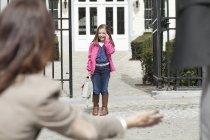 Mulher que dá a boa vinda morna à filha na porta da escola — Fotografia de Stock