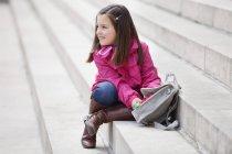 Kleines Mädchen Schultasche auf Treppen im freien öffnen — Stockfoto