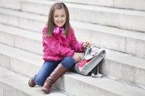 Porträt von lächelnden kleinen Mädchen öffnen Schultasche auf Treppen im Freien — Stockfoto