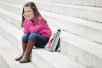 Kleine verträumte Schulmädchen sitzt auf Treppe im Freien — Stockfoto