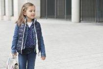 Écolière portant cartable tout en marchant dans la rue — Photo de stock