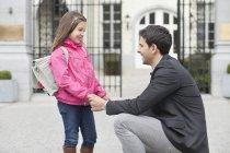 Riant homme parlant à sa fille, se tenant la main — Photo de stock