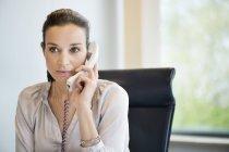 Businesswoman talking on landline phone in office — Stock Photo