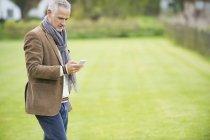 Homem elegante usando telefone celular no parque — Fotografia de Stock