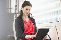 Donna che viaggia in autobus utilizzando un tablet digitale — Foto stock