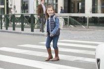 Scolaretta sorridente che attraversa una strada in città — Foto stock