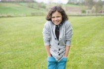 Портрет веселого мальчика, стоящего на зеленом осеннем поле — стоковое фото