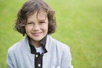 Портрет мальчика, улыбающегося в зеленом поле — стоковое фото