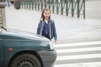 Smiling schoolgirl crossing a road in city — Stock Photo