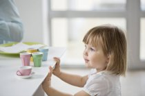 Cute little girl playing with  toy tea set from dining table — Stock Photo