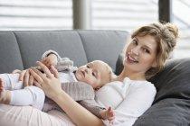 Усміхаючись молоду жінку, лежачи на дивані з baby дочка — стокове фото