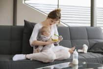 Woman feeding baby daughter while sitting on sofa at home — Stock Photo