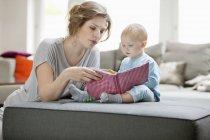 Frau zeigt Tochter Bilderbuch auf Sofa zu Hause — Stockfoto