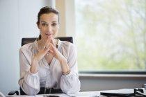 Ritratto di donna di affari sicura seduto in ufficio — Foto stock