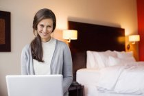 Portrait of smiling woman with laptop sitting in hotel room — Stock Photo