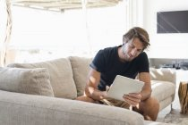 Smiling young man sitting on sofa and using digital tablet — Stock Photo