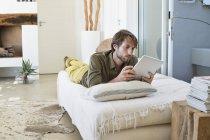Jeune homme utilisant une tablette numérique tout en étant couché sur le lit — Photo de stock