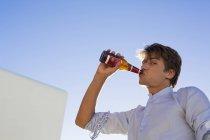 Giovane che beve birra contro il cielo blu — Foto stock
