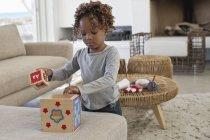 Niña jugando con juguetes en el sofá en casa - foto de stock