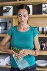 Donna che confeziona erbe per lo stoccaggio in cucina — Foto stock
