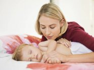 Mujer joven pensativo mirando lindo bebé durmiendo en la cama — Stock Photo