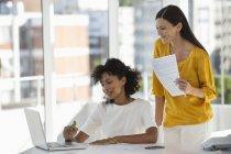 Две деловые женщины используют ноутбук у окна в офисе — стоковое фото