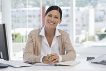Retrato de empresária confiante sorrindo para a mesa no escritório — Fotografia de Stock